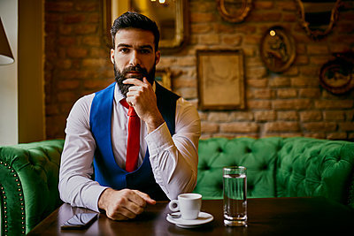 Portrait of fashionable young man sitting on couch in a cafe - p300m1549805 by Zeljko Dangubic