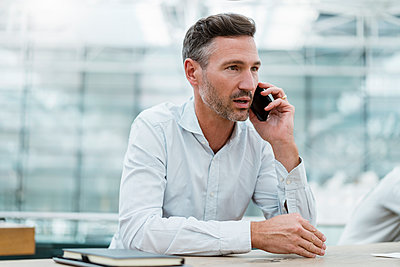 Portrait of businessman in a cafe talking on the phone - p300m2140224 von Daniel Ingold