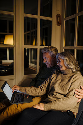 Senior couple using laptop on couch at home at night - p300m2155272 by Gustafsson