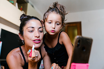 Mother and daughter applying lipstick while video recording in smart phone at home - p300m2213982 by Ezequiel Giménez