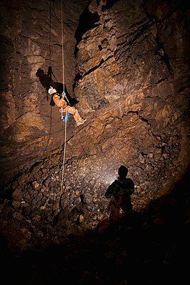 male athlete ascending a rope to exit a cave - p44212964f by Corey Hochachka