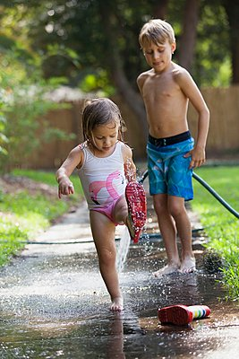Child in wellies playing in puddle of water, brother watching - p924m1125644f by Kinzie Riehm
