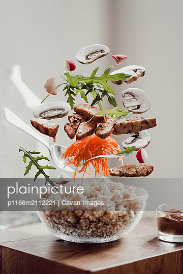 Close-up of various ingredients levitating over food in bowl on table - p1166m2112221 by Cavan Images