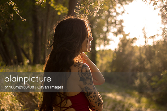 Portrait of a young girl in a red dress in a forest at sunset. Fantasy vibes - p1166m2130408 by Cavan Images