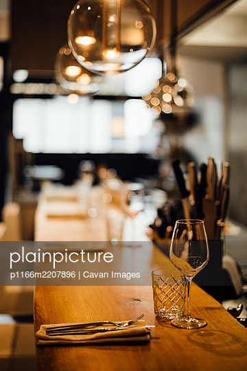 Restaurant kitchen interior: wooden bar counter, glasses, no people - p1166m2207896 by Cavan Images
