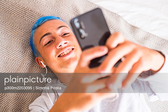 Young man with blue hair using smartphone and listening to music lying on bed - p300m2203095 by Simona Pilolla