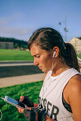 Female athlete with earphones and mobile - p1166m2247782 by Cavan Images