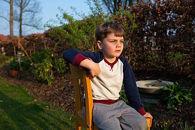 Junge sitzt auf einem Stuhl im Garten - p1308m2247514 von felice douglas