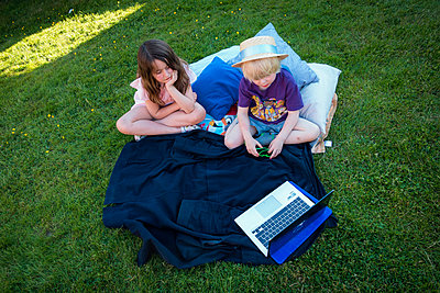 Little girl and little boy watching movie on laptop in garden - p1418m2013814 by Jan Håkan Dahlström