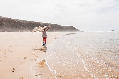 Mature woman walking on the beach lifting a blanket - p300m1189630 by Uwe Umstätter