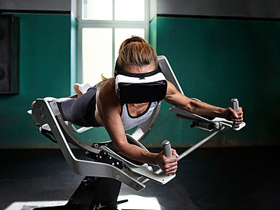 Woman wearing VR glasses using futuristic fitness machine - p300m1549356 by Christian Vorhofer