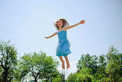 Carefree girl in dress jumping for joy in sunny backyard - p301m2075655 by Sven Hagolani