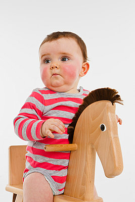 A baby girl on a rocking horse - p301m730550f by Julia Christe