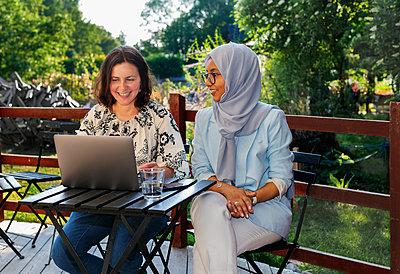 Female friends using laptop in garden - p312m2237122 by Pernille Tofte