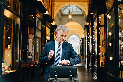 Mature businessman with bag looking at wristwatch while standing in city - p426m2186676 by Maskot