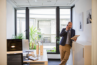 Caucasian businessman talking on cell phone in office - p555m1414279 by Lumina Images