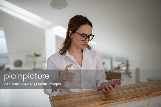 Young woman disinfecting smartphone at home - p1166m2234297 by Cavan Images