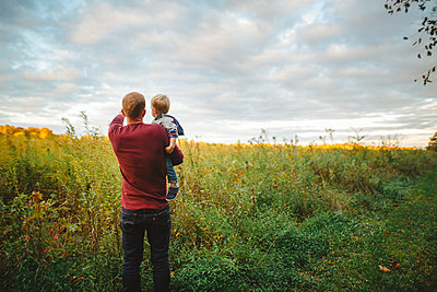 A father holds his small son in his arms in a field at sunset - p1166m2151939 by Cavan Images