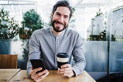 young man holding mug of coffee, Madrid, Spain - p300m2274054 von Eva Blanco