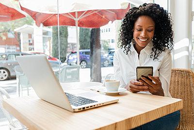 Business afro woman in coffee shop, Sevilla, Spain - p300m2299385 von Julio Rodriguez