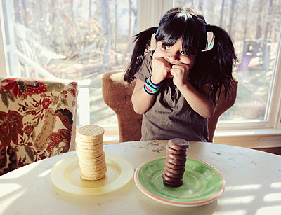 A girl trying to decide between two stacks of vanilla and chocolate cookies - p301m731160f by Tamara Lackey