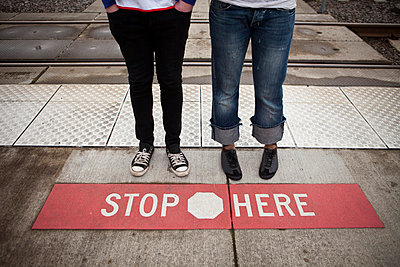 Urban couple stopped at STOP HERE sign on light rail tracks in metro area. - p343m963882 by Heath Korvola