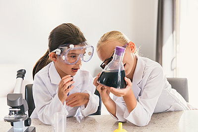Girls looking at liquid in conical flask - p924m1197147 by Matt Dutile