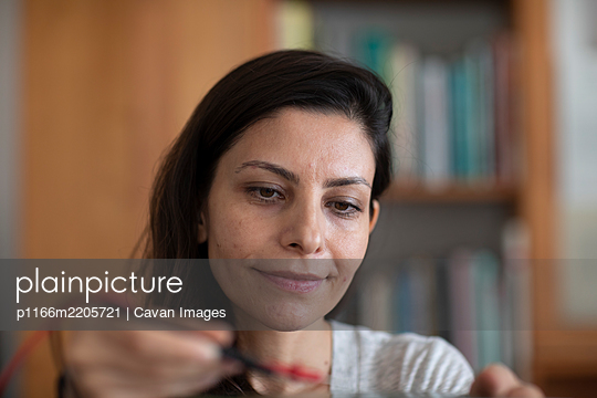 student female with tools in a library doing a try - p1166m2205721 by Cavan Images