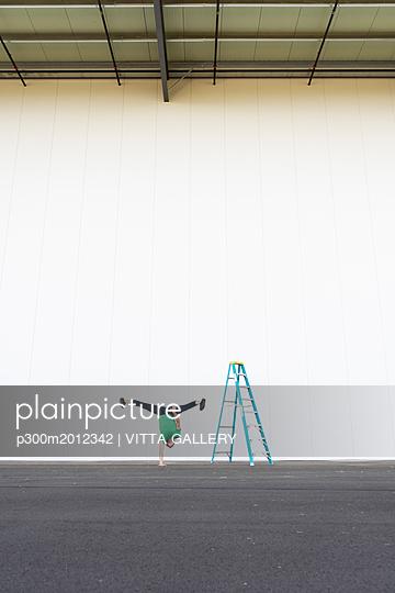 Acrobat training one-armed handstand next to ladder - p300m2012342 von VITTA GALLERY