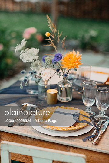 Place setting on festive laid table outdoors - p300m2059824 by Alberto Bogo