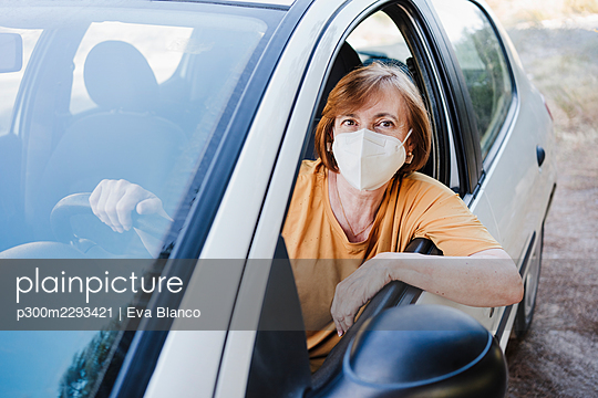 Senior woman with protective face mask sitting in car during COVID-19 - p300m2293421 by Eva Blanco