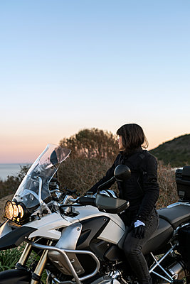 Female biker watching the panorama at sunset - p1165m1552717 by Pierro Luca