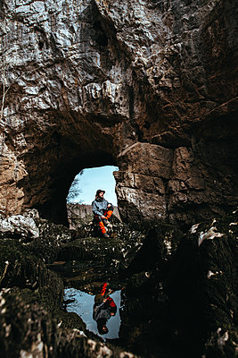 Man is sitting in front of a cave entrance - p1455m2081767 by Ingmar Wein
