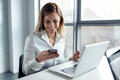 Businesswoman sitting in office working on laptop, using smartphone - p300m2170373 by Josep Suria