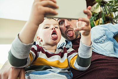 Father sticking out tongue with son talking selfie through smart phone at home - p300m2286868 by Uwe Umstätter