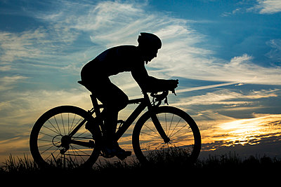 Germany, Mature man riding bicycle in sunset - p300m879406 by Stefan Schurr