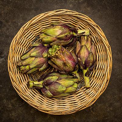 Artichokes in a wicker basket - p813m1481229 by B.Jaubert
