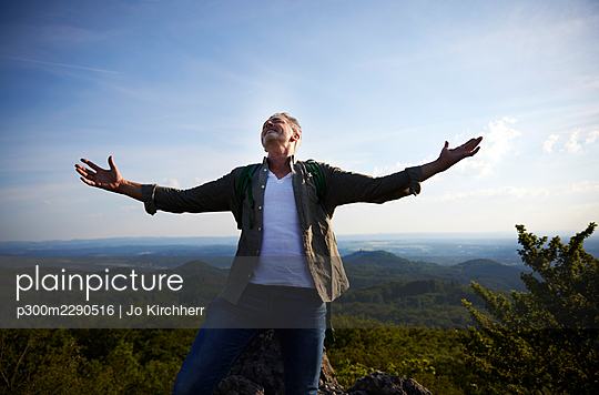 Carefree man standing with arms outstretched on mountain - p300m2290516 by Jo Kirchherr