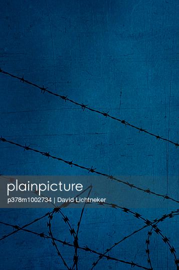 Razor wire against blue - p378m1002734 by David Lichtneker