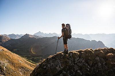Junger Wanderer genießt Ausblick in den Bergen  - p1142m2056445 von Frithjof Kjer