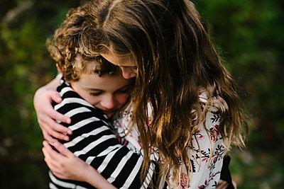 Close-up of loving siblings embracing at park - p1166m1555644 by Cavan Images