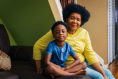 Portrait of cute smiling boy with grandmother at home - p1166m2279381 by Cavan Images