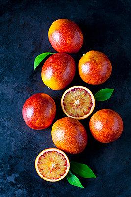 Whole and sliced blood oranges on dark ground - p300m1587353 von Dieter Heinemann