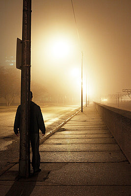 Man standing behind utility pole at night - p3721759 by James Godman