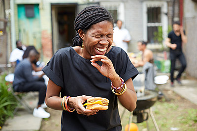 African American woman eating at backyard barbecue - p555m1409843 by Granger Wootz