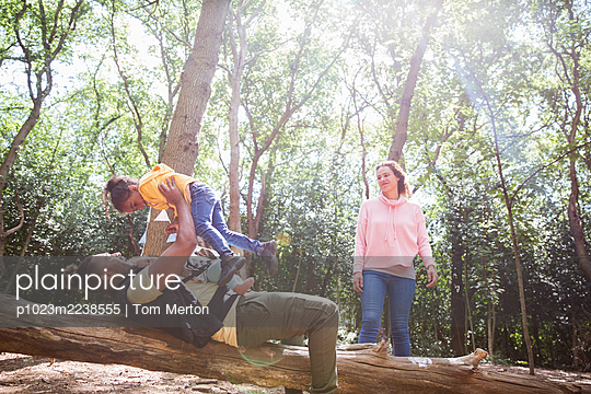 Family playing on fallen log below trees in sunny summer woods - p1023m2238555 by Tom Merton