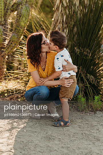 Full body view of mother bending down to kiss preschool aged son - p1166m2136673 by Cavan Images