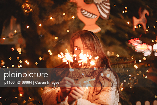Happy teenage girl holding sparklers standing by Christmas tree - p1166m2189664 by Cavan Images