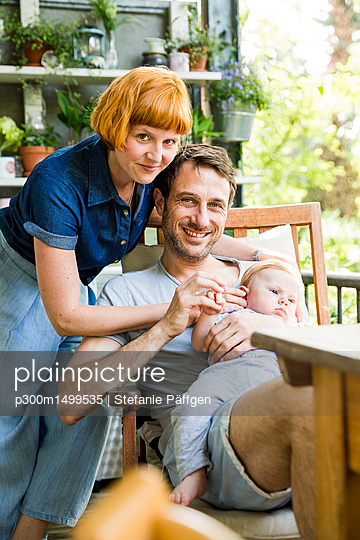 Happy couple with baby son together on balcony