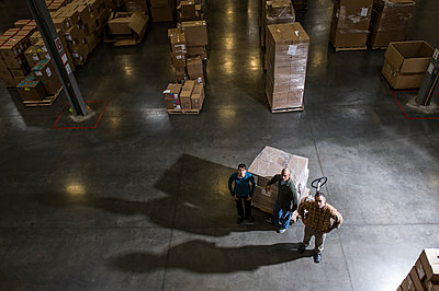 A group of three warehouse workers standing in the centre of a distribution warehouse. - p1100m2002281 by Mint Images